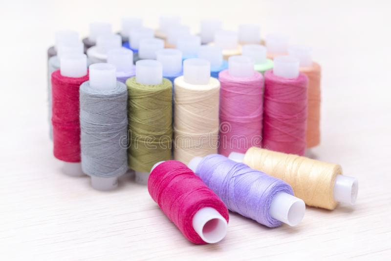 Threads on spools of different colors lie on a light wooden table. Three spools of thread are lying. royalty free stock photography