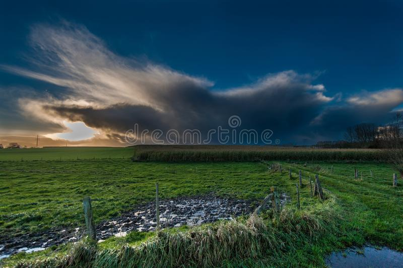 Threatening clouds in the western skies. A threating sky over and east flemish landscape, just before sunset stock images