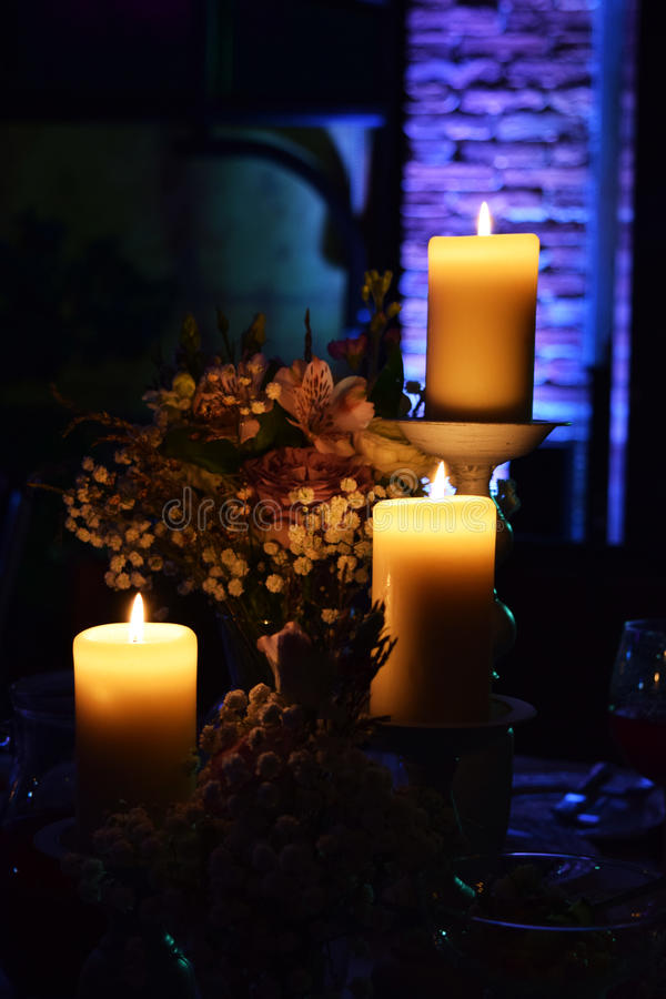 Three сandles in the dark, bouquet of flowers, wedding decor royalty free stock photo