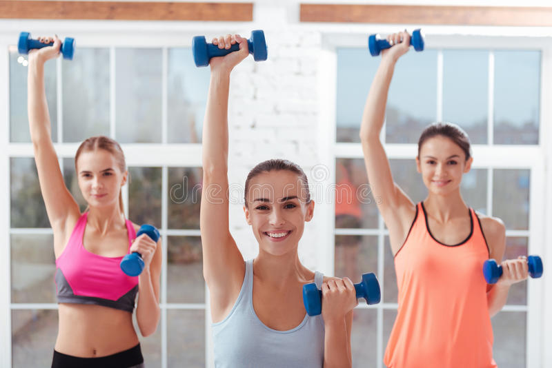 Three active women doing exercises for arms in gym royalty free stock photo