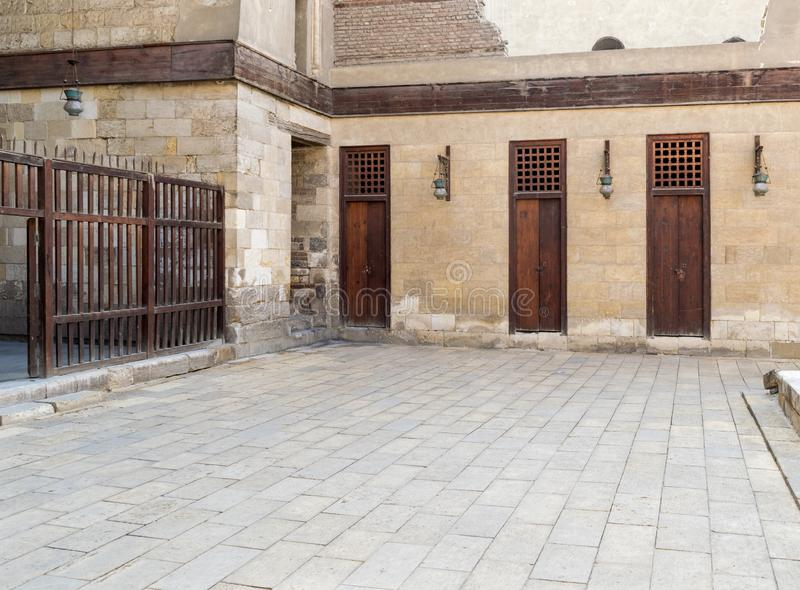 Three adjacent doors in a stone bricks wall and wooden fence, Sultan Al Nassir Qalawun Mosque. Three adjacent doors in a stone bricks wall and wooden fence at royalty free stock photo