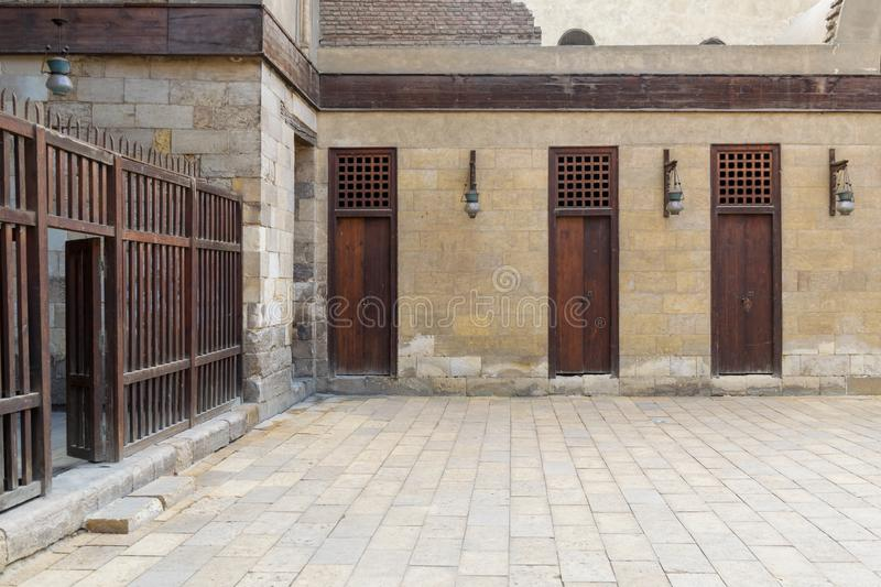 Three adjacent doors in a stone bricks wall and wooden fence, Sultan Al Nassir Qalawun Mosque. Three adjacent doors in a stone bricks wall and wooden fence at royalty free stock photos