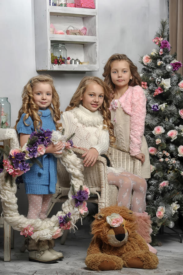 Three cute girls. Three adorable little girls waiting for Christmas royalty free stock image