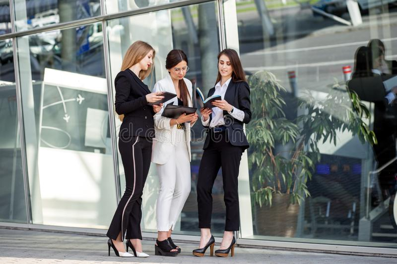 Three adult women discuss the task. Concept for business, marketing, finance, work, colleagues and lifestyle stock image