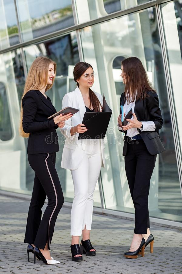 Three adult women discuss the task. Vertical. Concept for business, marketing, finance, work, colleagues and lifestyle royalty free stock photo