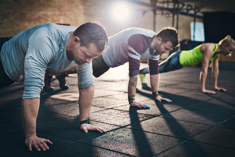 Three adults performing push up exercises stock photo