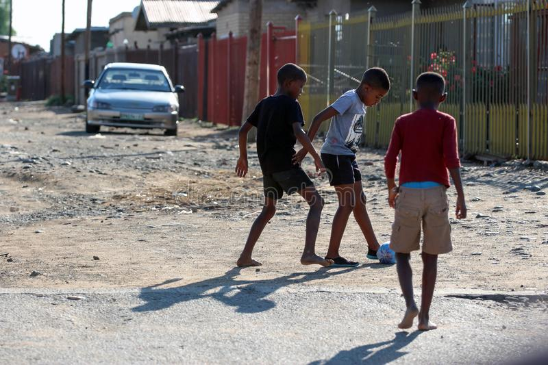 Black children from a suburb playing soccer - street photography royalty free stock photos