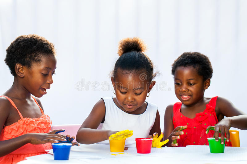 Three African kids painting together with hands. Portrait of three African kids painting with hands.Isolated against light background stock image