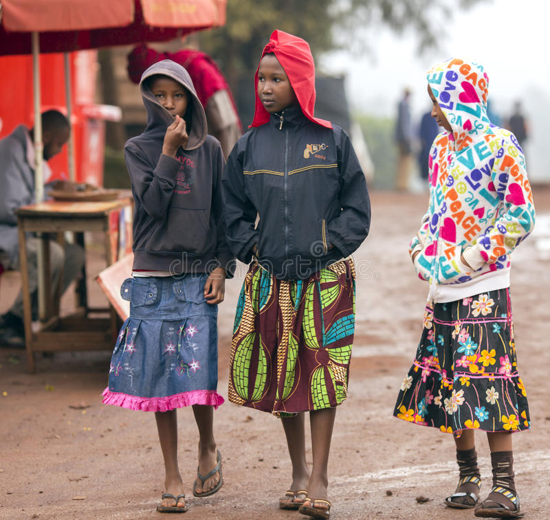 Three african poorly dressed young girls on the streets in Arusha. AFRICA, TANZANIA, MAY, 09, 2016 - Three african poorly dressed young girls on the streets in stock photo