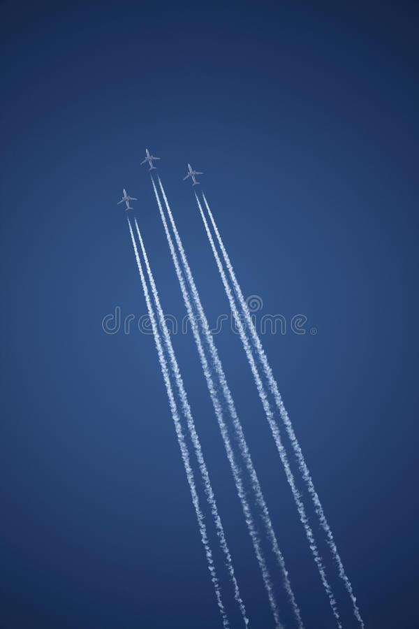 Three airplanes in formation. Three airplanes flying in formation with white stream trailing behind royalty free stock photography