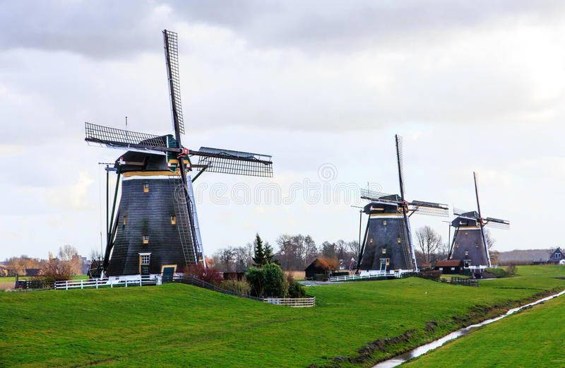 Three aligned windmills stock images