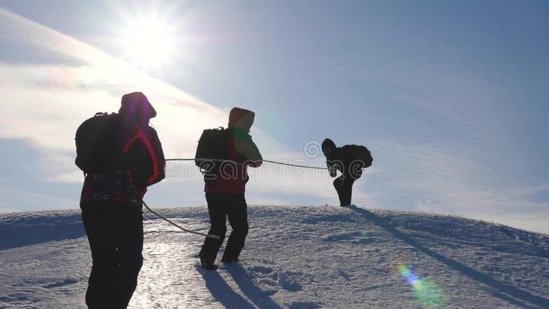Three Alpenists climb rope on snowy mountain. Tourists work together as team shaking heights overcoming difficulties. Silhouettes of travelers rise to their royalty free stock image
