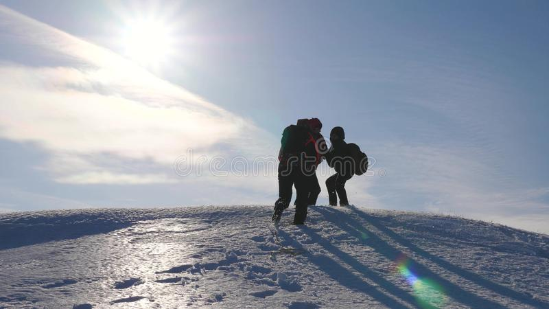 Three Alpenists climb rope on snowy mountain. Tourists work together as team shaking heights overcoming difficulties. Silhouettes of travelers rise to their stock photography
