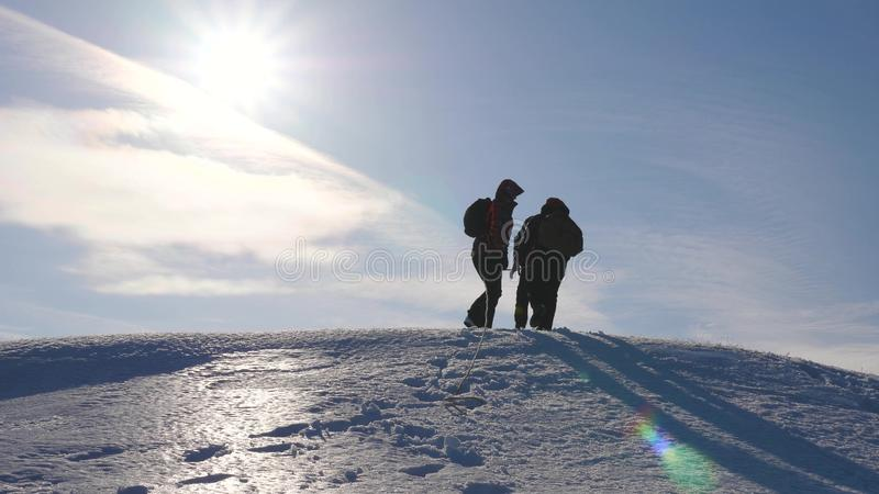 Three Alpenists climb rope on snowy mountain. Tourists work together as team shaking heights overcoming difficulties royalty free stock image