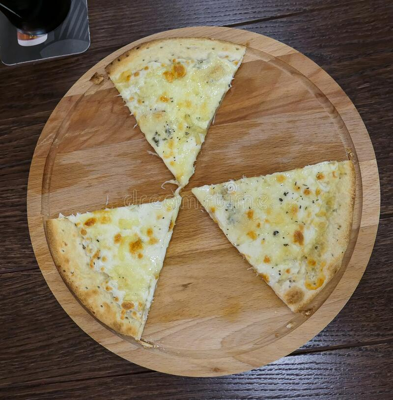 Three alternating pieces of pizza on wooden substrate looking similar to sign of radioactivity. On cafe table royalty free stock images