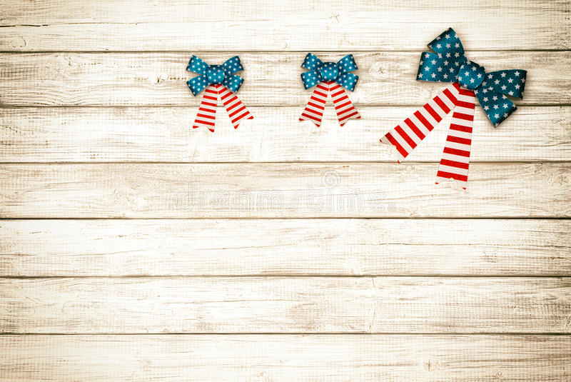 Three American Flag Bows on Rustic Wood Board Background with room or space for copy, text. Horizontal, sepia processing. Horizontal wood slat, plank boards with royalty free stock image