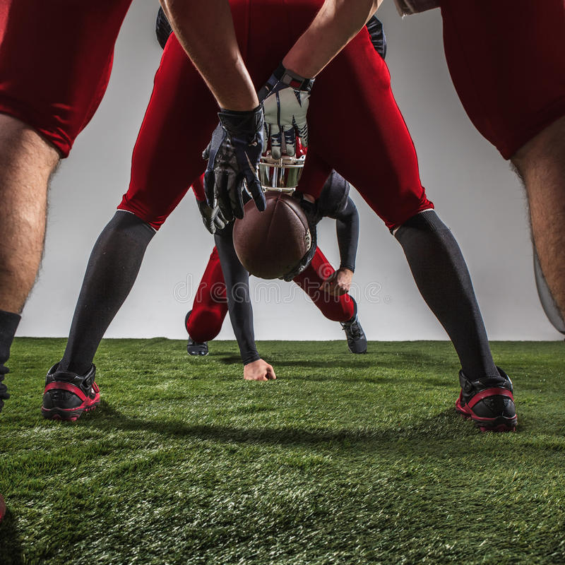 The three american football players in action. On green grass and gray background stock images