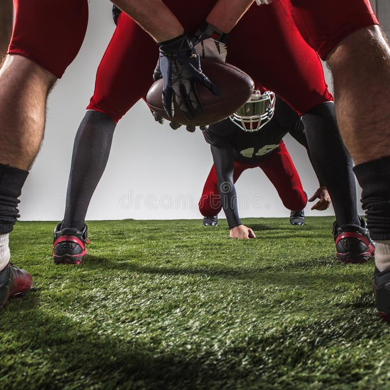 The three american football players in action. On green grass and gray background stock photography