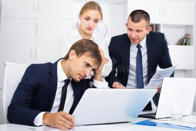 Three annoyed coworkers in firm office. Three annoyed coworkers experiencing business failure in firm office royalty free stock images