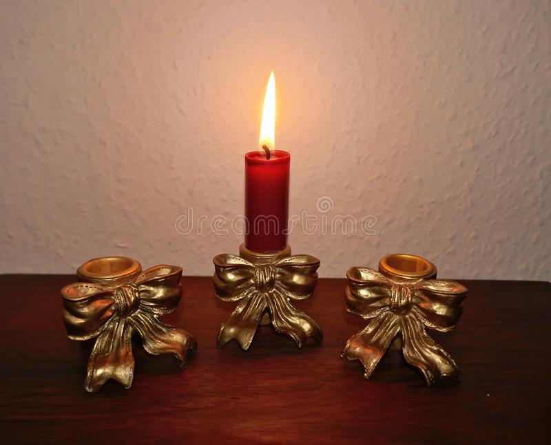 .Three antique golden candlesticks decorated with bows on a mahogany shelf in front of a bright wall. In one is a burning red cand royalty free stock image