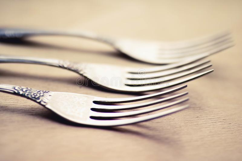 Three antique silver forks close up view. Blurred background stock photography