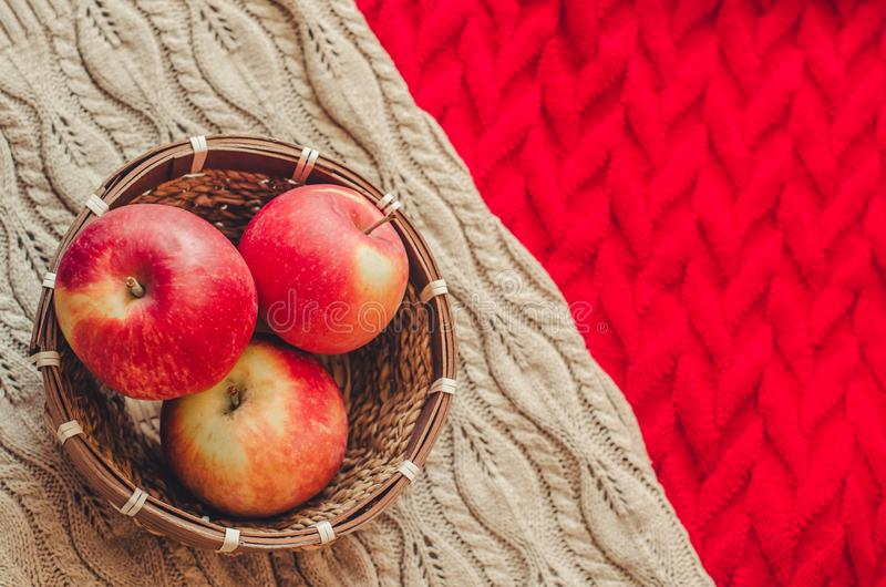Three apples in the basket on knitted background royalty free stock photography