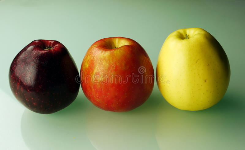 Three apples on green background royalty free stock images
