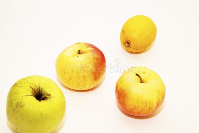 Three apples and lemon on a white background. Healthy foods rich in vitamins. Still life. Three apples and a yellow lemon on a white background. Healthy foods royalty free stock photos