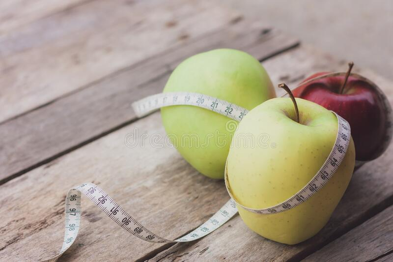 Three apples with measuring tape on wooden background. Diet and healthy life loss weight concept. Three apples with measuring tape on wooden background. Diet stock photo
