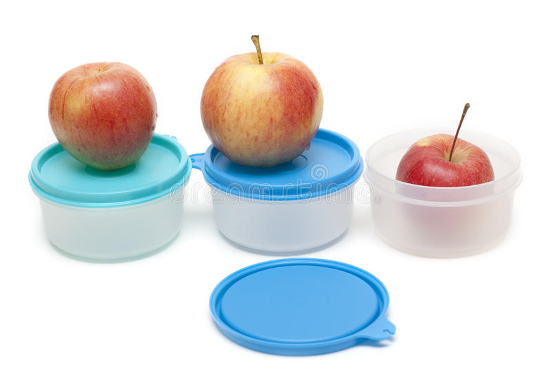 Three apples and plastic containers. On white background stock photo