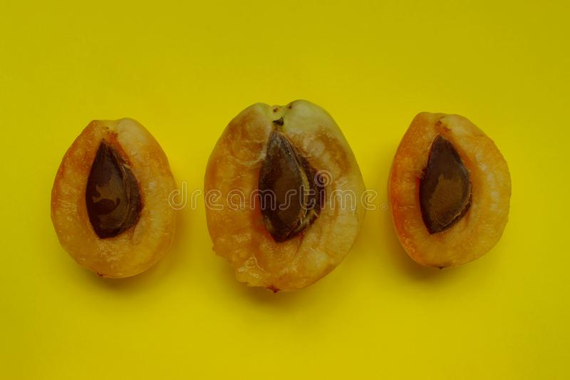 Three apricot halves over yellow background. Abstract food background. Colorful background stock photos