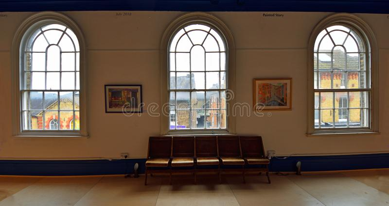 Three Arched Windows and bench from inside looking out. royalty free stock photos