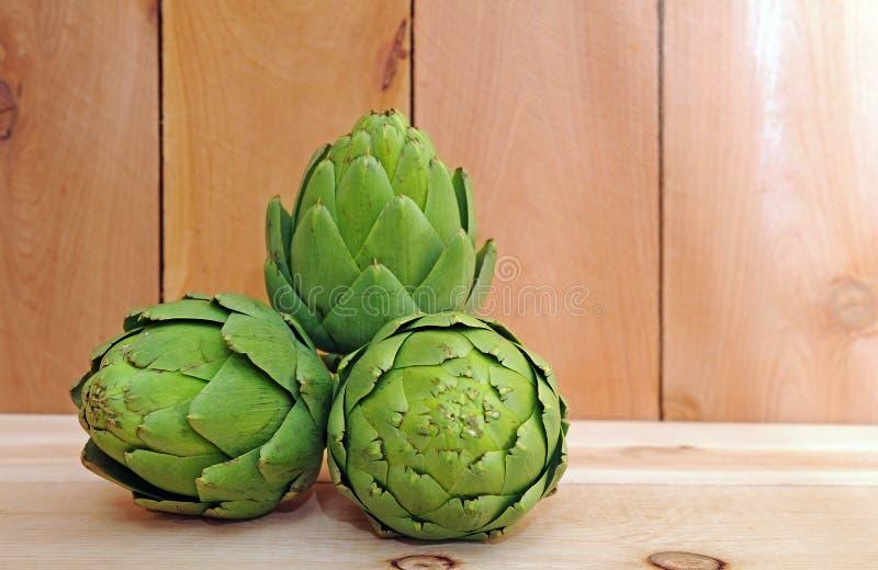 Three artichoke. On wooden shelf royalty free stock photo