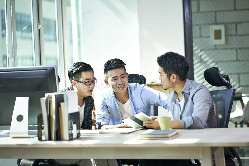 Three asian business men working together in office royalty free stock images