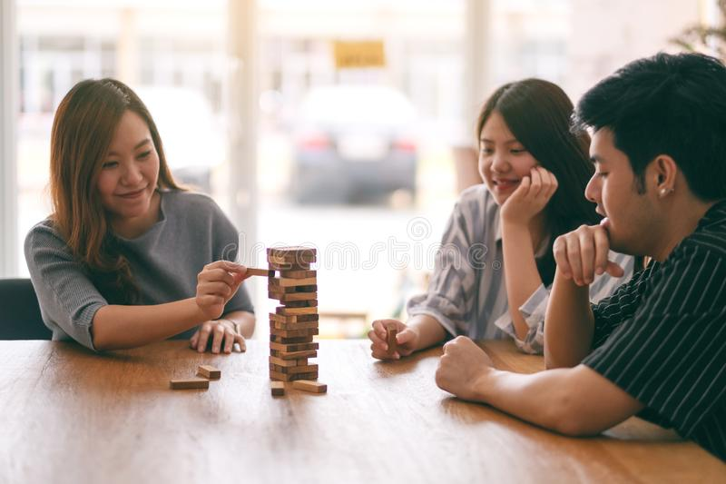 Three asian friends sitting and playing Tumble tower wooden block game together. With feeling happy royalty free stock images