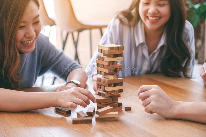 Three asian friends sitting and playing Tumble tower wooden block game together. With feeling happy royalty free stock image