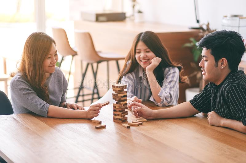 Three asian friends sitting and playing Tumble tower wooden block game together. With feeling happy stock photo