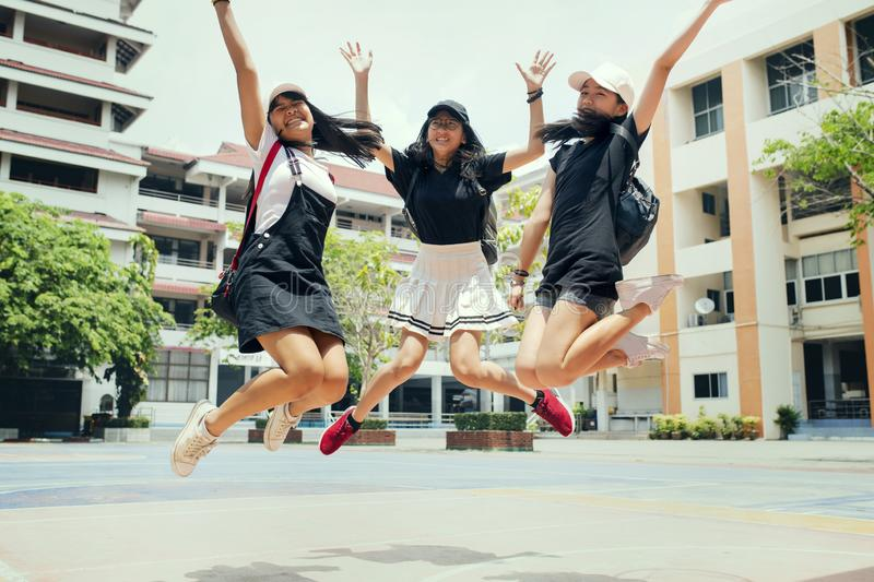 Three asian teenager jumping mid air with happiness emotion against school building background. Three asian teenager  jumping mid air with happiness emotion stock photo