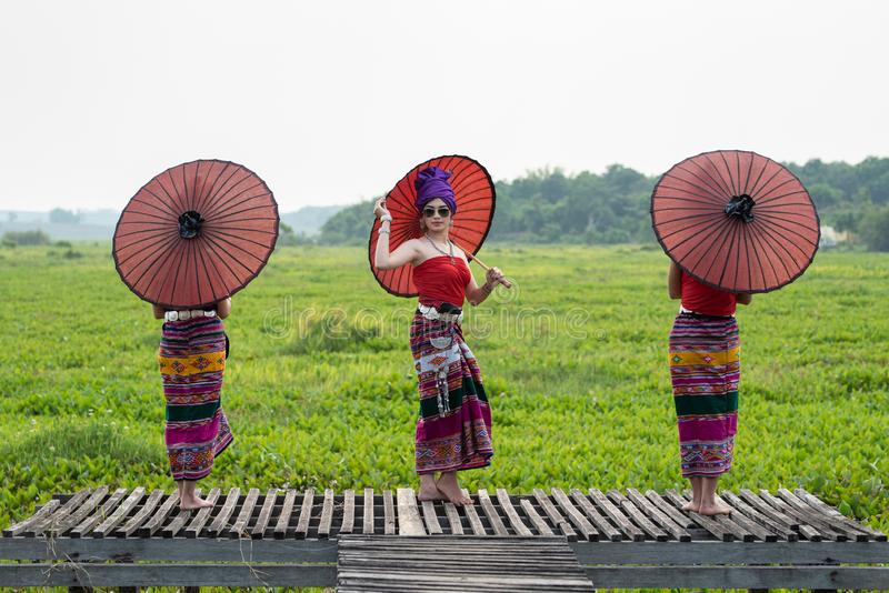 Three Asian Thai Lanna woman in traditional dress hand hold paper umbrella act like model on wooden bamboo bridge with overcast. Three Asian Thai Lanna women in royalty free stock photo