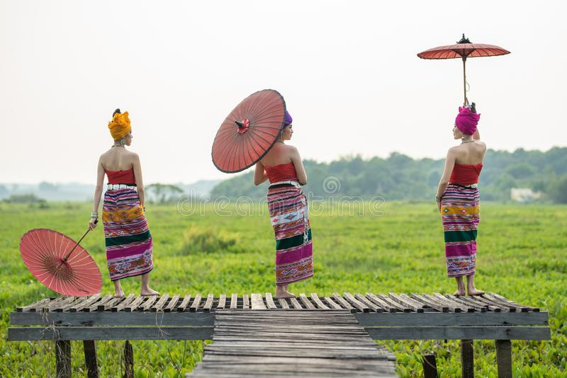 Three Asian Thai Lanna woman in traditional dress hand hold paper umbrella act like model on wooden bamboo bridge with overcast. Three Asian Thai Lanna women in royalty free stock photos