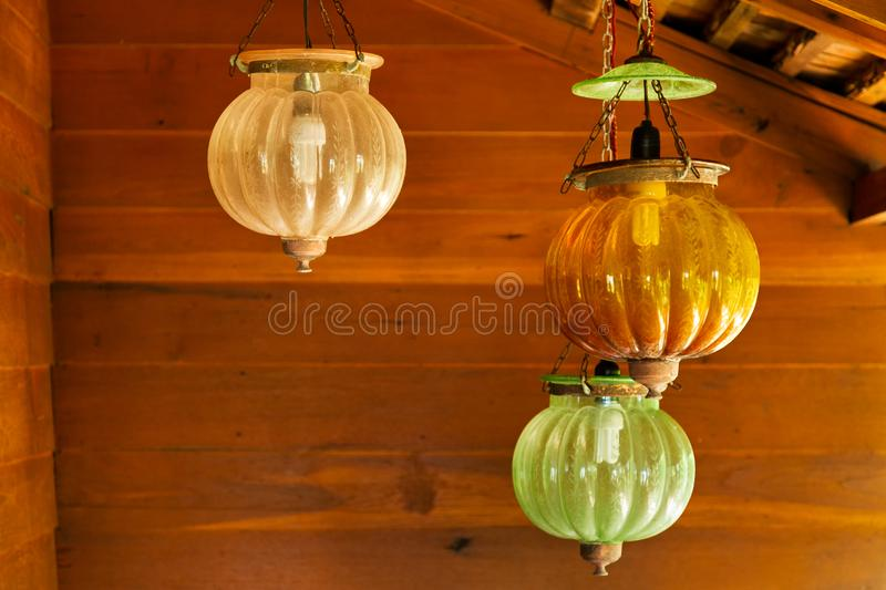 Three asian vintage hanging lamps with wooden wall background stock photography