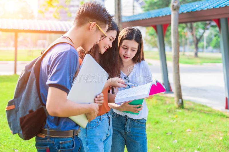 Three Asian young campus people tutoring and preparing for final stock photography