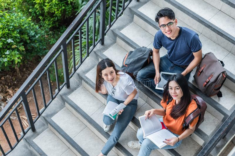 Three Asian young campus students enjoy tutoring and reading boo stock photos
