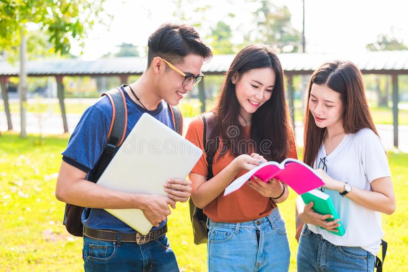 Three Asian young campus students enjoy tutoring and reading books together. Friendship and Education concept. Campus school and stock images