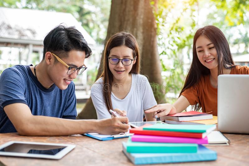 Three Asian young campus students enjoy tutoring and reading books together. Friendship and Education concept. Campus school and royalty free stock photo