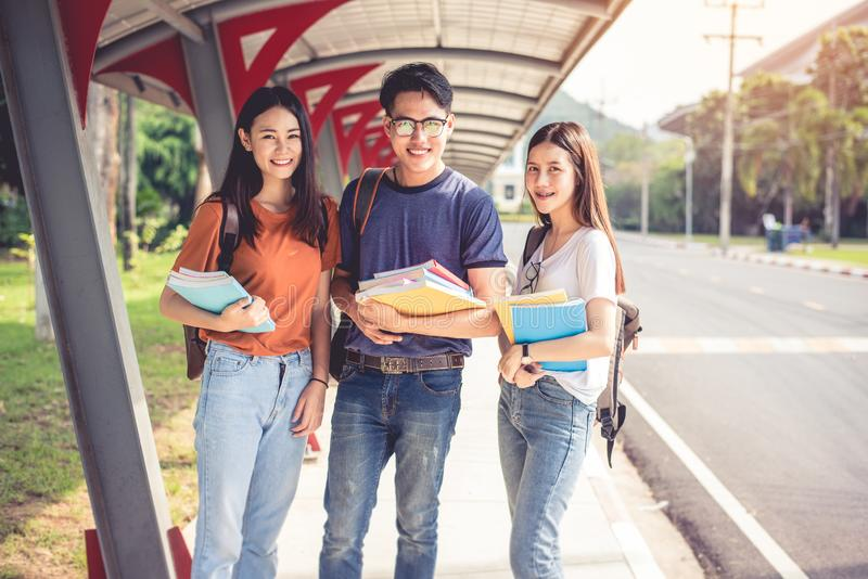 Three Asian young campus students enjoy tutoring and reading books together. Friendship and Education concept. Campus school and stock photos
