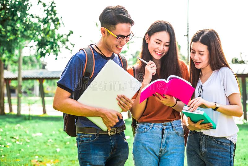 Three Asian young campus students enjoy tutoring and reading books together. Friendship and Education concept. Campus school and stock image