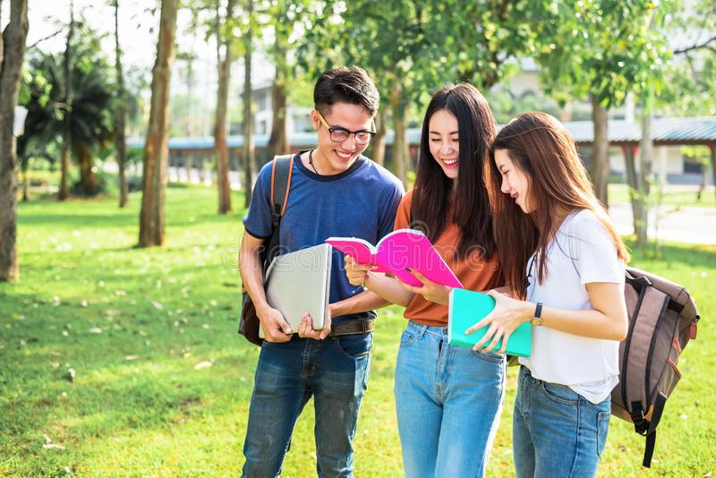 Three Asian young campus students enjoy tutoring and reading books together. Friendship and Education concept. Campus school and royalty free stock image