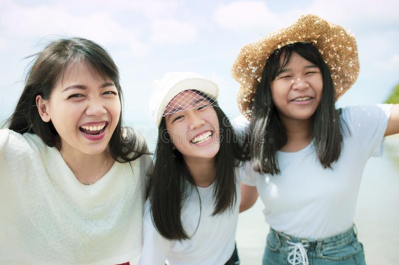Three asian younger woman and teen happiness on sea beach stock image