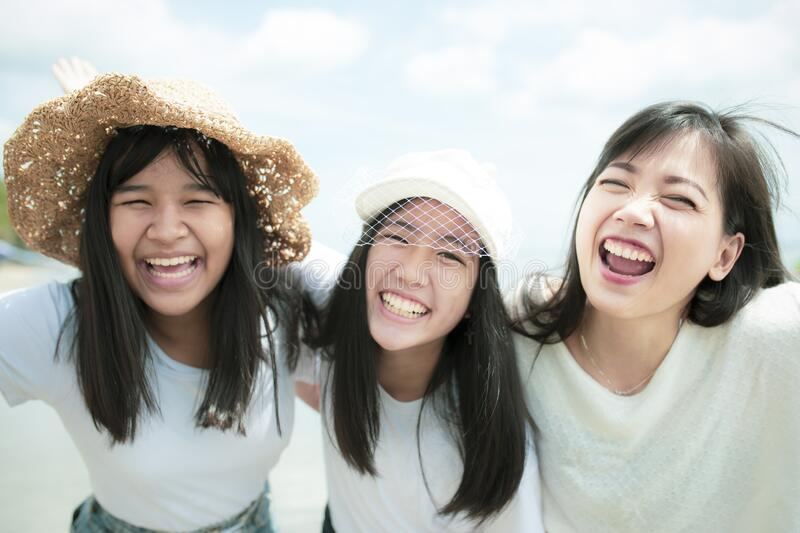 Three asian younger woman and teen happy on sea beach stock image